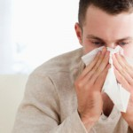 A man with seasonal allergic rhinitis blows his nose