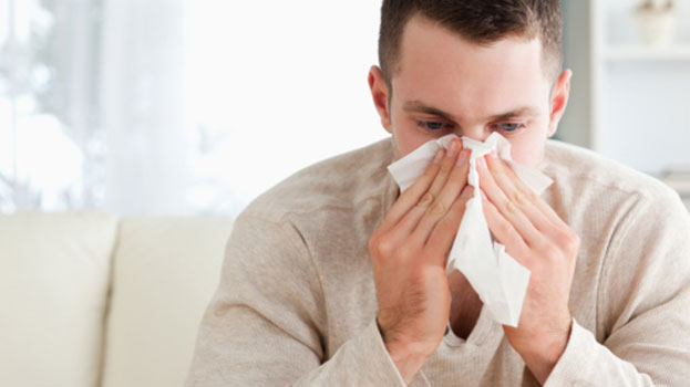 A man with seasonal allergic rhinitis blows his nose. Sneezing is an allergy symptom common to Hay Fever sufferers.