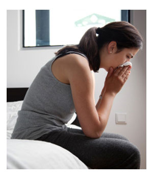 A woman with hay fever is blowing her nose on bed